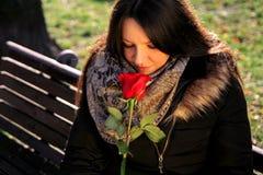 Hübsches Mädchen riecht Rotrose und genießt den Geruch stockfotos