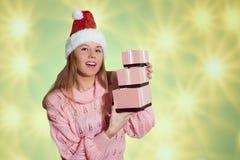 Hübsches Mädchen in rotem Sankt-Hut, der rosa Geschenk hält Stockfoto