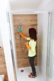 Hübsches Mädchen säubert Badezimmer Stockfotografie