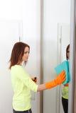 Hübsches Mädchen säubert Badezimmer Stockfotos