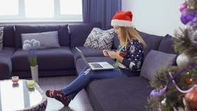 Hübsches Mädchen in Sankt-` s Hut macht das Weihnachtseinkaufen durch Internet stock video