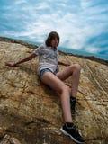 Hübsches Mädchen sitzt auf dem Stein auf See- und Himmelhintergrund stockfoto