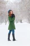 Hübsches Mädchen steht am Wintertag im Park im Freien Stockbilder