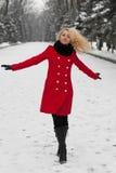 Hübsches Mädchen tanzt in den Schnee lizenzfreie stockfotografie