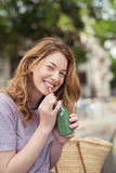Hübsches Mädchen-trinkender Saft, die Kamera betrachtend Stockfoto