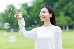 Hübsches Mädchen und bunte Blasen Lizenzfreie Stockfotos
