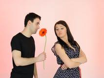 Hübsches Mädchen und flirtenmann mit einer Blume Stockfotos