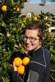 Hübsches Mädchen wählt Orangen aus Stockbild