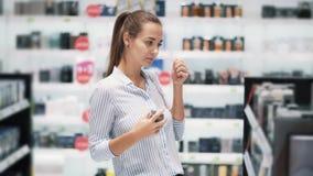 Hübsches Mädchen wählt Parfüm in den Kosmetik kaufen, sprühten es auf Prüfvorrichtung, Zeitlupe stock video footage