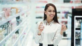Hübsches Mädchen wählt Parfüm in den Kosmetik kaufen, sprühten es auf Prüfvorrichtung, Zeitlupe stock video