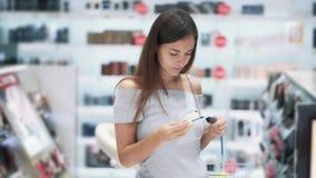 Hübsches Mädchen wählt Wimperntusche in den Kosmetik kaufen, öffnen und schnüffeln sie, Zeitlupe stock footage