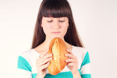 Hübsches Mädchenanhalten und beißender Brotlaib Lizenzfreie Stockbilder