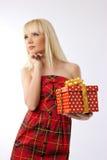 Hübsches Mädchenholding-Weihnachtsgeschenk im roten Kleid Lizenzfreie Stockbilder