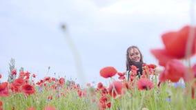 Hübsches Mädchentanzen auf einem Mohnblumengebiet, das glücklich lächelt Verbindung mit Natur Freizeit in der Natur Bl?hende Mohn stock footage