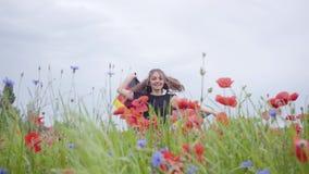 Hübsches Mädchentanzen in einer Mohnblumenfeld-Holdingflagge von Deutschland in den Händen draußen Verbindung mit Natur, Patrioti stock video footage