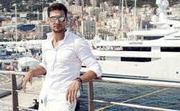 Hübsches männliches Modell, das vor einer Luxusyacht aufwirft stockbilder
