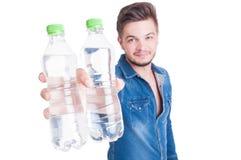 Hübsches männliches Modell, das zwei Flaschen kaltes Wasser anbietet stockbilder