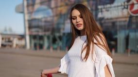 Hübsches Mode-Modell im weißen Kleid wirft mit Einkaufstaschen vor einem modernen Glasgebäude auf stock video