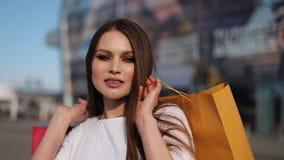 Hübsches Mode-Modell im weißen Kleid wirft mit Einkaufstaschen vor einem modernen Glasgebäude auf stock video footage