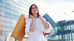 Hübsches Mode-Modell im weißen Kleid wirft mit Einkaufstaschen vor einem modernen Glasgebäude auf stock footage