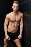 Hübsches, muskulöses hemdloses Lehnen des jungen Mannes an der Fliesenwand Lizenzfreies Stockbild