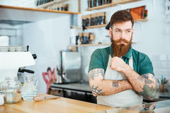 Hübsches nachdenkliches Mann barista, das seinen Bart und Denken berührt Lizenzfreie Stockfotos