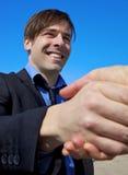 Hübsches rüttelndes Handlächeln des Geschäftsmannes glücklich Lizenzfreie Stockfotos