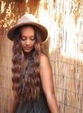 Hübsches Sonnenbräunemädchen in einem Hut durch einen Bambuszaun Lizenzfreie Stockfotografie