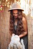 Hübsches Sonnenbräunemädchen in einem Hut durch einen Bambuszaun, der einen Hund streichelt Stockbild