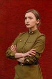 Hübsches starkes Mädchen in der sowjetischen Uniform des Zweiten Weltkrieges an rotem w Lizenzfreies Stockbild