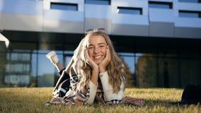 Hübsches stilvolles zur Kamera schauendes und bei der Entspannung lächelndes Mädchen auf dem Gras stock footage
