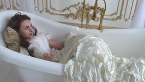 Hübsches tragendes weißes Weinlesekleid des jungen Mädchens, das im ampty Bad ersucht um Handy liegt Nette Frau, die an spricht stock video footage