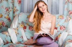 Hübsches und junges blondes Mädchen, sitzend auf einer weißen Couch und lesen a Lizenzfreie Stockbilder