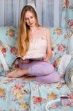 Hübsches und junges blondes Mädchen, sitzend auf einer weißen Couch und lesen a Stockfoto