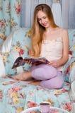 Hübsches und junges blondes Mädchen, sitzend auf einer weißen Couch und lesen a Stockbilder