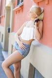 Hübsches und natürliches Mädchen lehnt sich an der Wand Stockbild