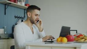 Hübsches Unterhaltungstelefon des jungen Mannes und Anwendung der Laptop-Computers, die morgens in der Küche nach Frühstück sitzt stock footage