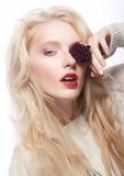Hübsches weibliches Gesicht. Blondes langes Haar. Rote Blume Stockbild