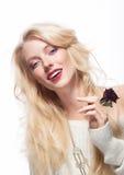 Hübsches weibliches Gesicht. Blondes langes Haar. Rote Blume Lizenzfreie Stockfotografie