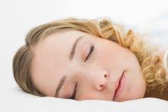 Hübsches zufriedenes blondes Lügen im Bett, das bei geschlossenen Augen liegt Stockfotos