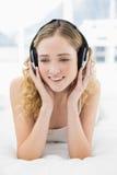 Hübsches zufriedenes blondes Lügen im Bett, das Musik hört Stockfoto