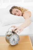 Hübsches zufriedenes blondes Lügen im Bett, das Wecker abstellt Stockfotografie