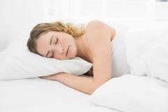 Hübsches zufriedenes blondes Lügen im Nickerchen machenden Bett Lizenzfreie Stockbilder