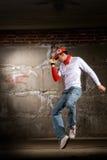 Hüftehopfenjungentanzen in der modernen Art über grauer Wand Stockbilder