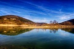 Hügel über See mit Reflexionen stockbild