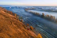 Hügel des trockenen Grases des Herbstes und nebeliges blaues Tal SONNENAUFGANG Stadt am Hintergrund stockfotografie