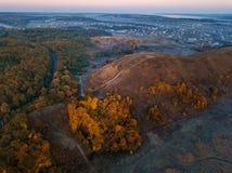 Hügel mit schönen Herbstbäumen Blauer Nebel Sonnenaufgangstimmungsmoment Stadt am Hintergrund Brummenluftfoto stockfotos