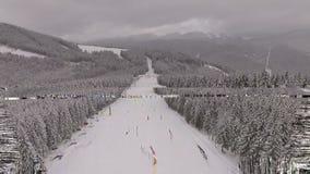 Hügel mit vielen Leuten bei Schneewetter im Berg - Skiort stock video footage