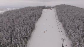 Hügel mit vielen Leuten bei Schneewetter im Berg - Skiort stock footage