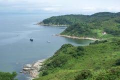 Hügel werden mit grünem Wald, blauem Himmel und einem Fischerboot im Urlaub bedeckt Stockfotografie